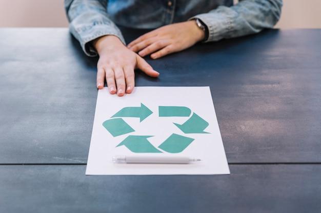 Nahaufnahme der hand mit bereiten ikone auf papier mit stift über holztisch auf Kostenlose Fotos