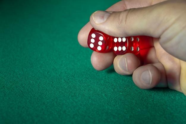 Nahaufnahme der hand rote würfel mit einer gewinnenden kombination auf grünem stoff in einem kasino halten. Premium Fotos