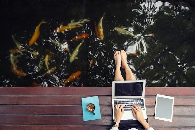 Nahaufnahme der hand unter verwendung des laptops und der tablette mit kaffeetasse Premium Fotos