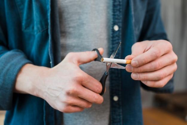 Nahaufnahme der handausschnittzigarette des mannes mit scissor Kostenlose Fotos