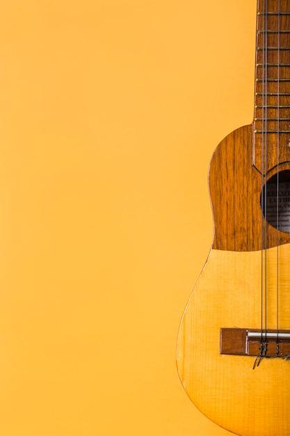 Nahaufnahme der hölzernen ukulele auf gelbem hintergrund Kostenlose Fotos