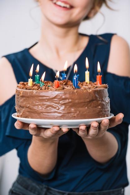 Nahaufnahme der holdingplatte des mädchens hand des schokoladenkuchens mit brennenden kerzen Kostenlose Fotos