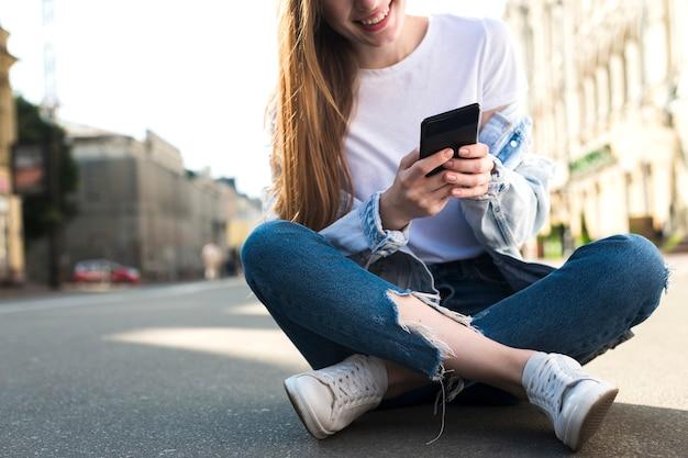 Nahaufnahme der jungen frau sitzend auf straße unter verwendung des mobiltelefons Kostenlose Fotos