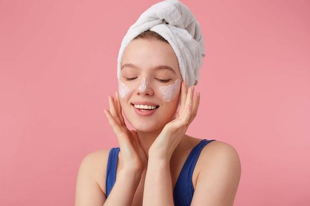 Nahaufnahme der jungen netten fröhlichen frau mit natürlicher schönheit mit einem handtuch auf dem kopf nach dem duschen, steht und setzt gesichtscreme mit geschlossenen augen auf. Kostenlose Fotos