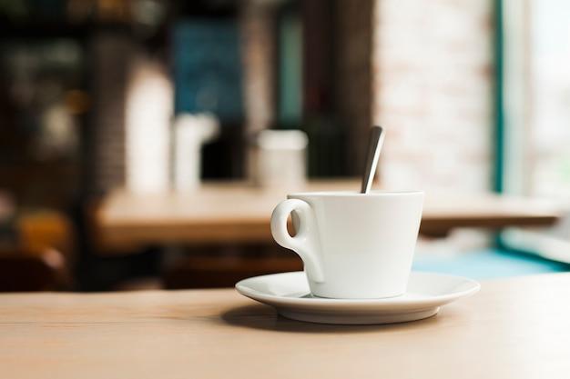 Nahaufnahme der kaffeetasse mit untertasse auf holztisch in der cafeteria Kostenlose Fotos