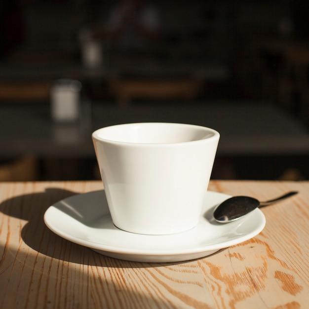 Nahaufnahme der kaffeetasse und des löffels auf schreibtisch Kostenlose Fotos