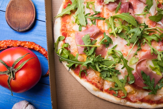 Nahaufnahme der köstlichen speck- und rucola-pizza im kasten mit knoblauch; tomaten und chili auf dem tisch Kostenlose Fotos