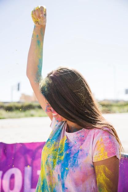 Nahaufnahme der lächelnden jungen frau, die holi farbe über ihrem kopf besprüht Kostenlose Fotos