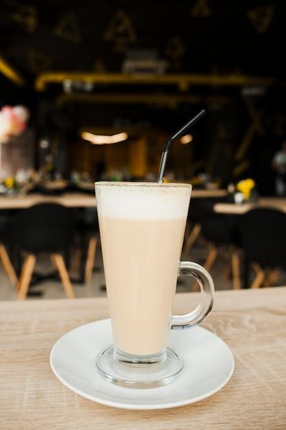 Nahaufnahme der lattekaffeetasse mit stroh und untertasse auf hölzernem schreibtisch Kostenlose Fotos
