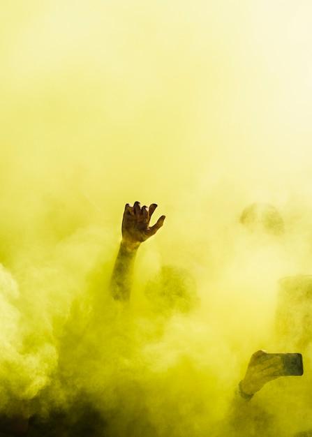 Nahaufnahme der leute tanzen und in der gelben explosion der holi farbe Kostenlose Fotos