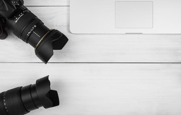 Nahaufnahme der linse mit zwei kameras mit laptop auf weißem holztisch Kostenlose Fotos