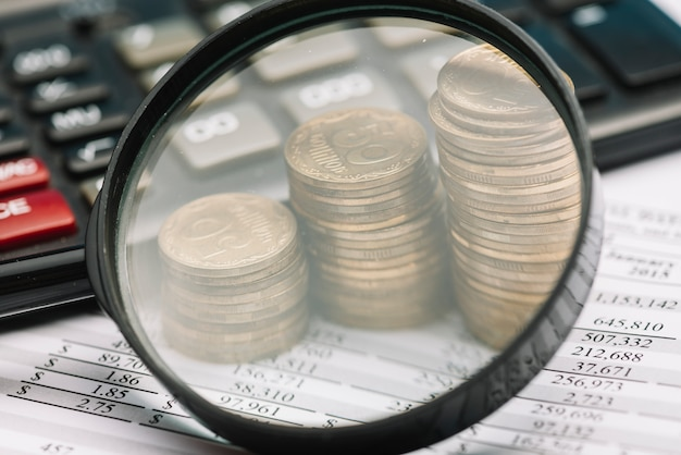 Nahaufnahme der lupe über den stapel prägt und taschenrechner auf finanzbilanz Kostenlose Fotos