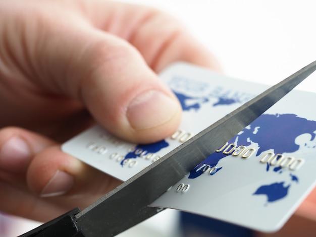 Nahaufnahme der männlichen hände, die plastikkarte halten und mit schere in zwei hälften schneiden. geschäftsmann, der bankkarte mit karte der welt und der zahl ändert. kreditorenbuchhaltung und geldkonzept Premium Fotos
