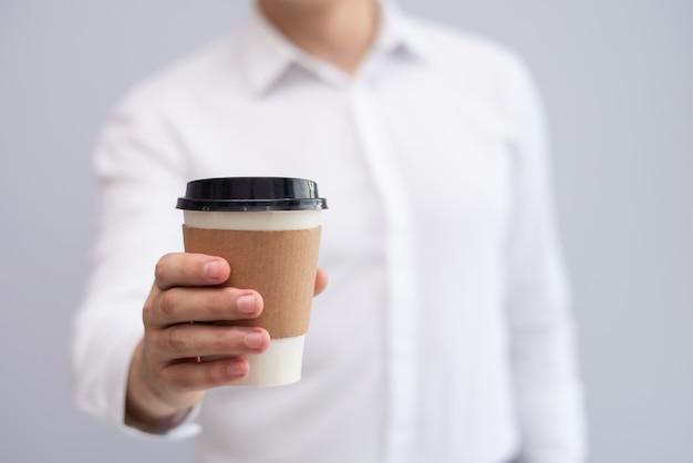 Nahaufnahme der männlichen hand mitnehmerkaffee halten Kostenlose Fotos