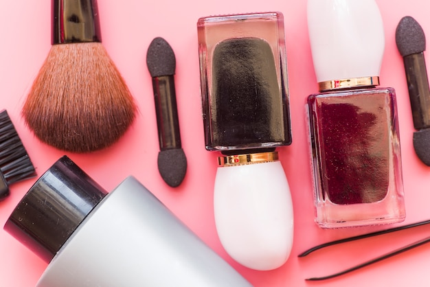 Nahaufnahme der make-upbürste; kosmetikprodukt und pinzette auf rosa hintergrund Kostenlose Fotos