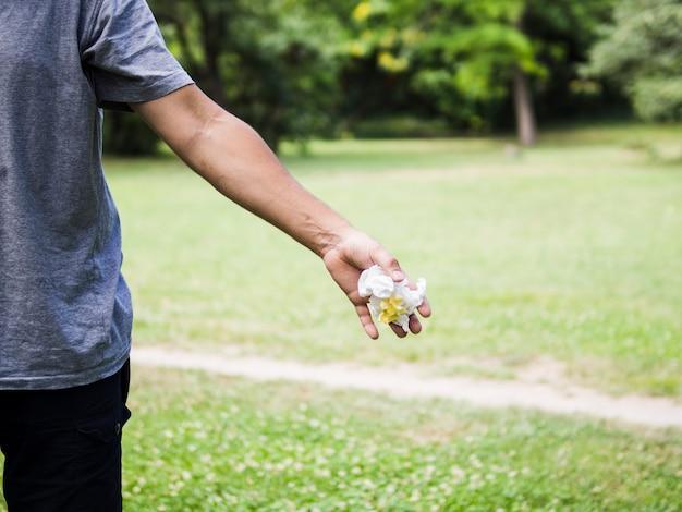Nahaufnahme der mannhand zerknittertes papier im park werfend Kostenlose Fotos