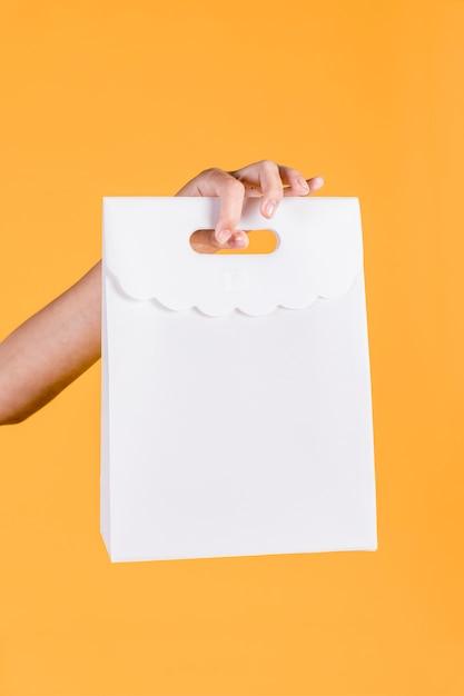 Nahaufnahme der menschlichen hand weiße papiertüte auf gelbem wandhintergrund halten Kostenlose Fotos