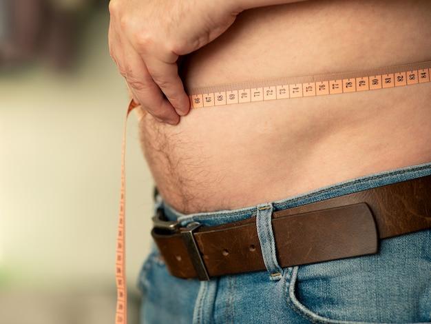 Nahaufnahme der messung eines männlichen bauches mit einem schneidermeter. der mann zeigt seinen nackten bauch Premium Fotos
