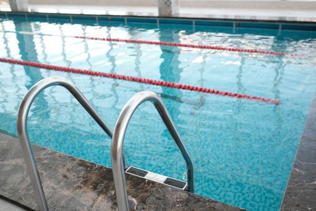 Nahaufnahme der metallpooltreppe mit geländer für den eintritt in das schwimmbad im fitnessstudio Premium Fotos
