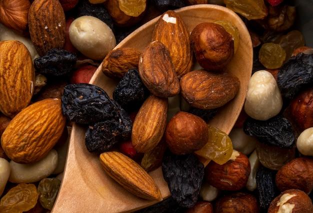 Nahaufnahme der mischung von nüssen und getrockneten früchten mandel und schwarzen rosinen Kostenlose Fotos