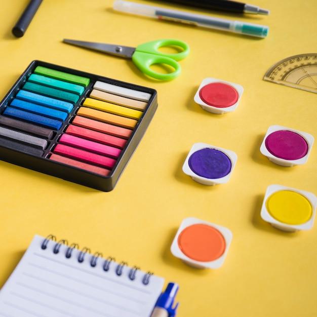 Nahaufnahme der multi farbigen aquarellfarbe und der schreibwaren auf gelbem hintergrund Kostenlose Fotos