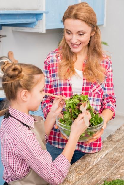 Nahaufnahme der mutter und der tochter, die den salat zubereiten Kostenlose Fotos