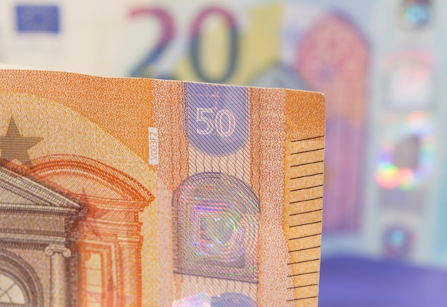 Nahaufnahme der neuen banknote von fünfzig euro mit einer anderen rechnung zwanzig, unscharf im hintergrund. Premium Fotos