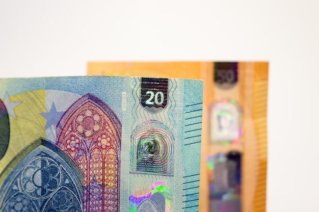 Nahaufnahme der neuen banknote von zwanzig euro mit einer anderen rechnung fünfzig, unscharf im hintergrund. Premium Fotos
