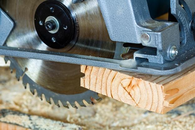 Nahaufnahme der neuen modernen starken elektrischen kreissäge, die hölzerne planken schneidet. tischlerwerkzeug, bau, reparatur und gebäudekonzept. Premium Fotos