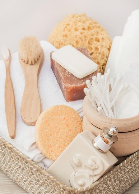 Nahaufnahme der parfümflasche; bürste; schwamm; seife; wattestäbchen; handtuch und körperpeeling im tablett Kostenlose Fotos