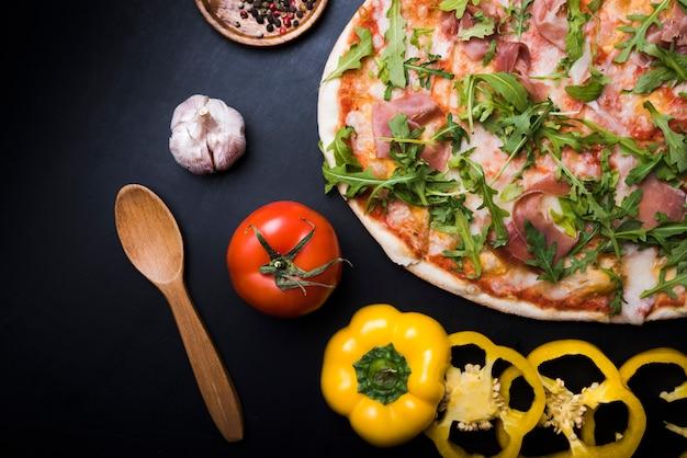 Nahaufnahme der pizza mit rucola-blättern; scheiben gelbe paprika; tomaten- und knoblauchknolle über schwarzem hintergrund Kostenlose Fotos