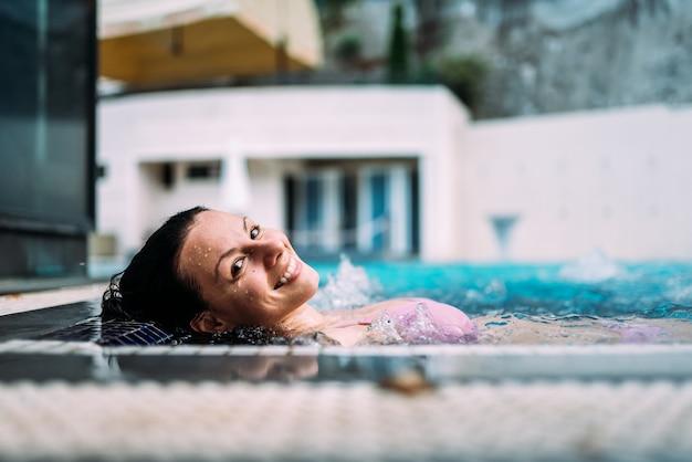Nahaufnahme der schönen frau draußen entspannend in einer heißen wanne. Premium Fotos