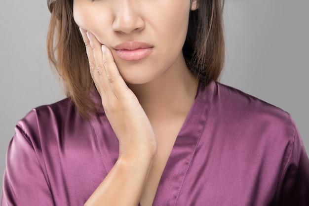 Nahaufnahme der schönen jungen frau, die unter zahnschmerzen, zahnmedizinischer gesundheit und sorgfalt leidet. Premium Fotos