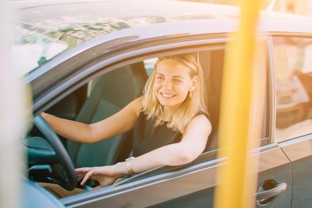 Nahaufnahme der schönen lächelnden jungen frau, die das auto fährt Kostenlose Fotos