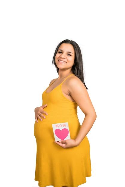 Nahaufnahme der schwangeren frau, die grußkarte hält Kostenlose Fotos