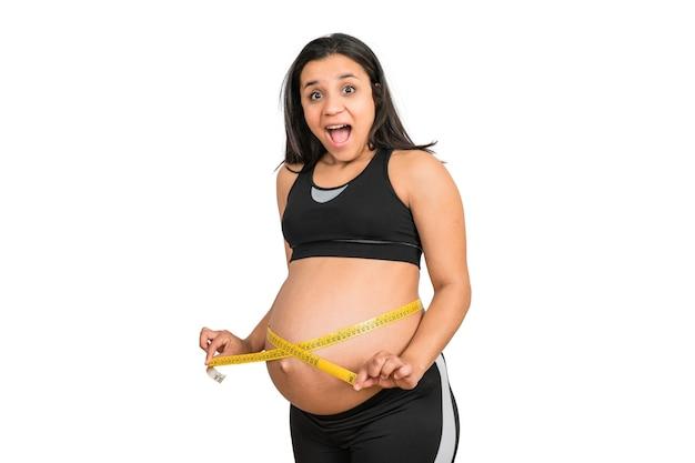 Nahaufnahme der schwangeren frau unter verwendung des maßbandes, um babyentwicklung zu überprüfen Kostenlose Fotos