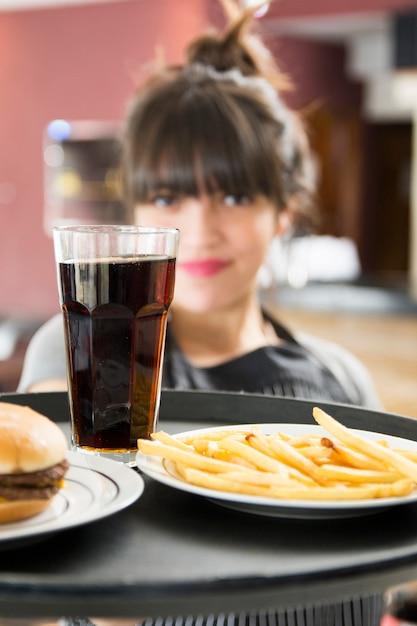 Nahaufnahme der serviergetränke der weiblichen kellnerin mit burger und pommes-frites Kostenlose Fotos