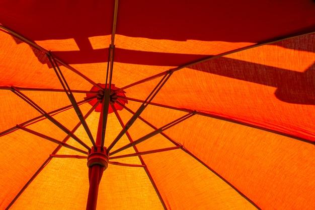 Nahaufnahme der struktur des orangefarbenen sonnenschirms aus holz für geschütztes sonnenlicht. Premium Fotos