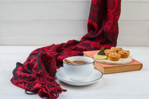 Nahaufnahme der tasse tee, weiße kekse in einem teller mit rotem schal und einem buch Kostenlose Fotos