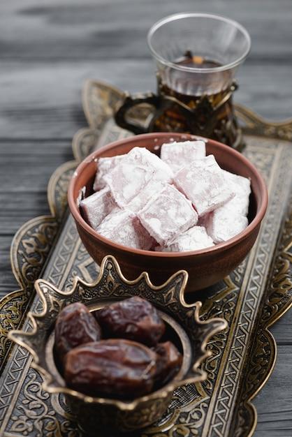 Nahaufnahme der traditionellen türkischen freude lukum; datteln und tee auf metallischem tablett Kostenlose Fotos