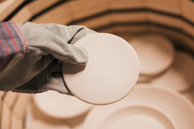Nahaufnahme der tragenden handschuhe der frau hand, die keramische platten halten Kostenlose Fotos