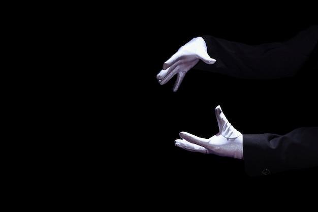 Nahaufnahme der tragenden weißen handschuh des zauberers hand gegen schwarzen hintergrund Kostenlose Fotos