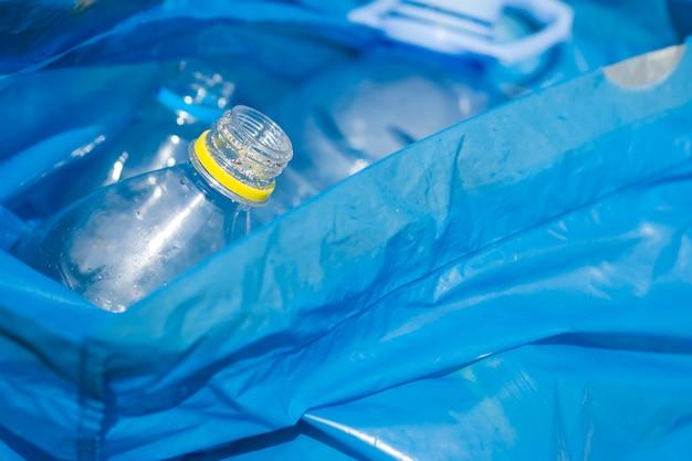 Nahaufnahme der überschüssigen plastikflasche in der blauen abfalltasche Kostenlose Fotos