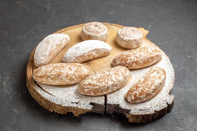 Nahaufnahme der verschiedenen arten von köstlichen keksen auf einem kaputten schneidebrett im dunkeln Kostenlose Fotos