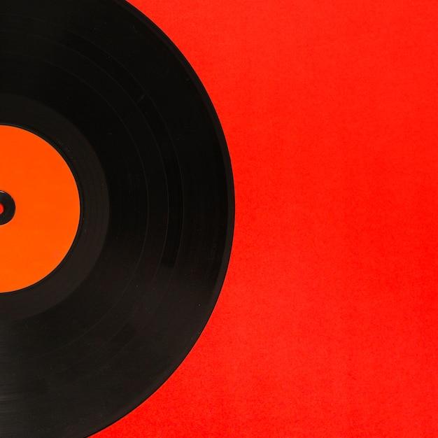 Nahaufnahme der vinylaufzeichnung über dem roten hintergrund Kostenlose Fotos