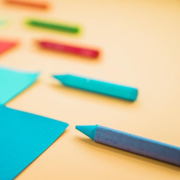 Nahaufnahme der wachszeichenstiftfarbe und des kartenpapiers gegen gelben hintergrund Kostenlose Fotos