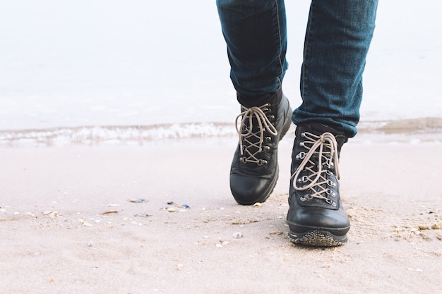 Nahaufnahme der weiblichen beine in den winterstiefeln sind auf dem strand Premium Fotos