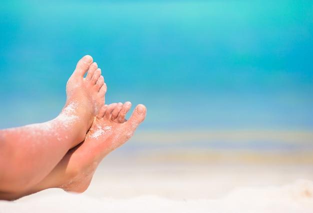 Nahaufnahme der weiblichen füße am weißen sandstrand Premium Fotos