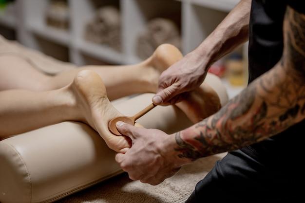 Nahaufnahme der weiblichen hände, die fußmassage tun. frau, die reflexmassage-fußmassage im wellness-spa genießt. Premium Fotos