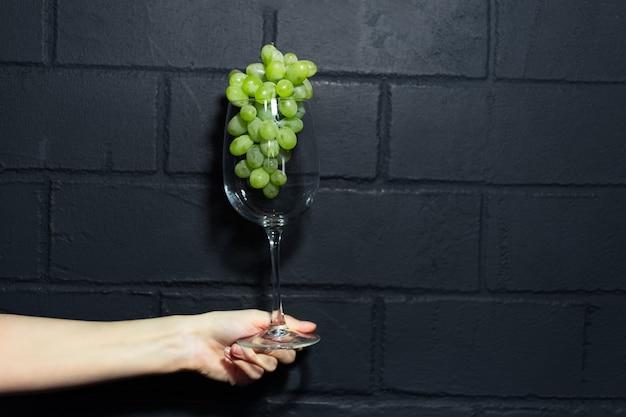 Nahaufnahme der weiblichen hand, die ein weinglas mit grünen trauben innen auf hintergrund der schwarzen backsteinmauer hält. Premium Fotos